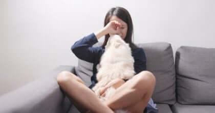 Nainen leikkii koiransa kanssa.