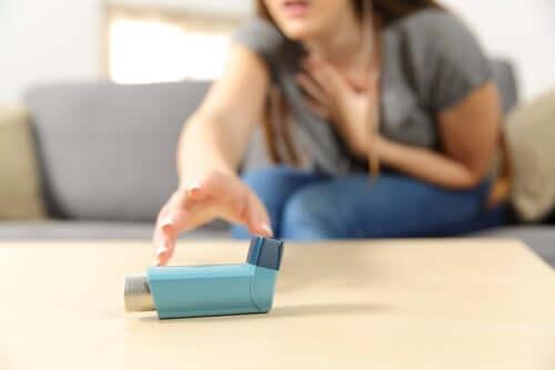 Nainen kurkottaa astmapiippuun.