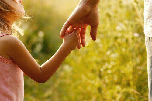 Lapsi pitää vanhempaansa kädestä.