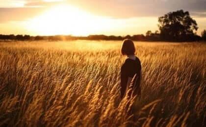 Nainen viljapellossa etsimässä onnea.