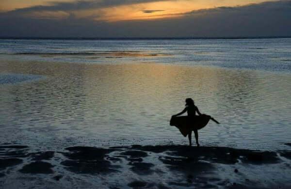 Nainen on yksin rannalla auringonlaskussa.