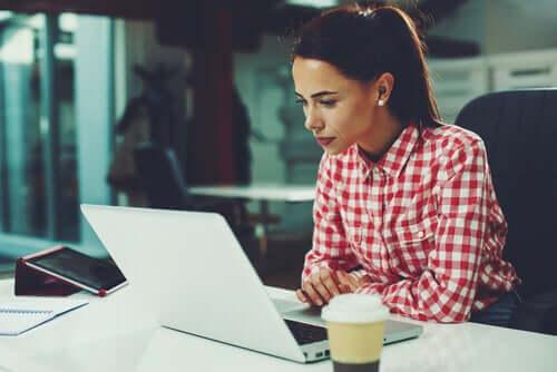Nainen tekee töitä läppärillään.
