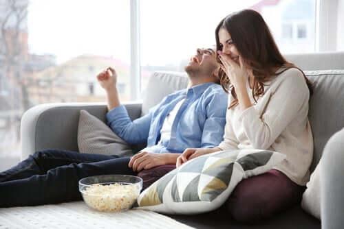 Pariskunta katsoo sohvalla hauskaa elokuvaa.