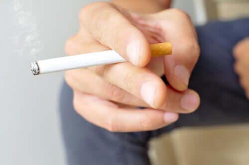 Miehellä on tupakka kädessä.