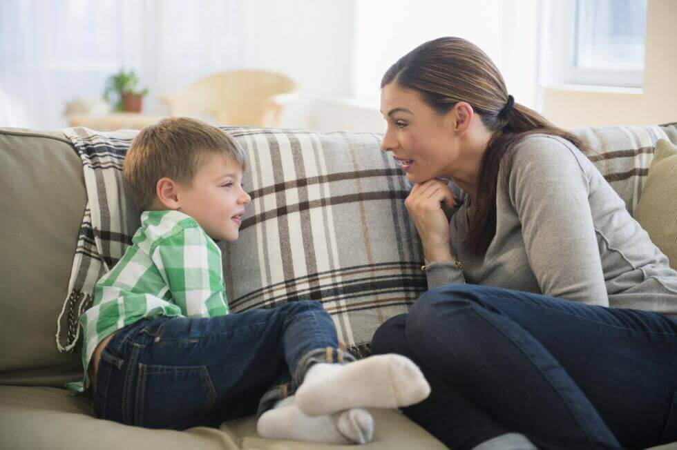 Poika ja äiti keskustelevat sohvalla