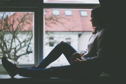 Nainen istuu ikkunalaudalla.