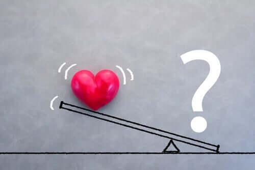 Sydän ja kysymysmerkki vaakalaudalla.