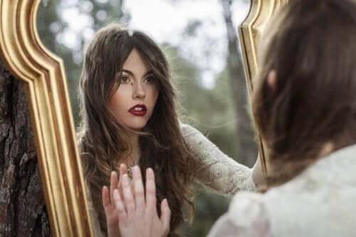 Nainen katselee itseään peilistä.