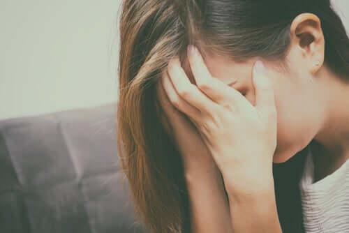 Epätoivoinen nainen hautaa kasvot käsiinsä.