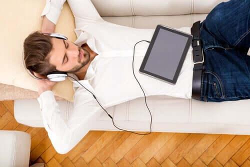 Mies sohvalla kuuntelemassa jotakin.