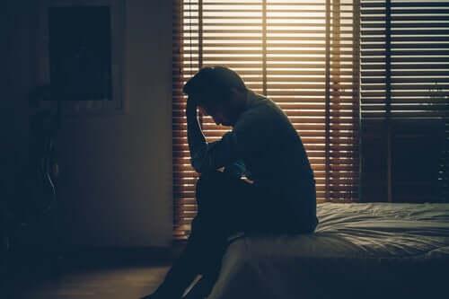 Surullinen mies istuu sängyllä pimeässä huoneessa.